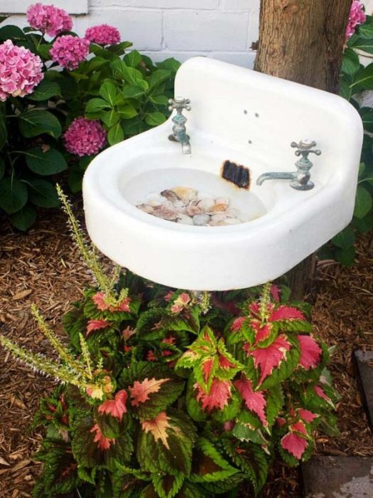 Прекрасный вариант размещения старинной раковины на природе в саду.