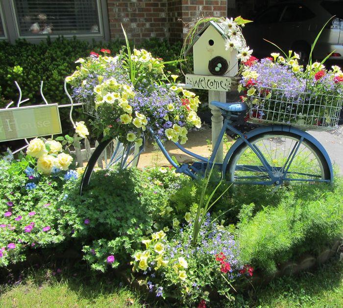 Украшена глядка с цветами велосипедом, который тоже весь укутан цветами.