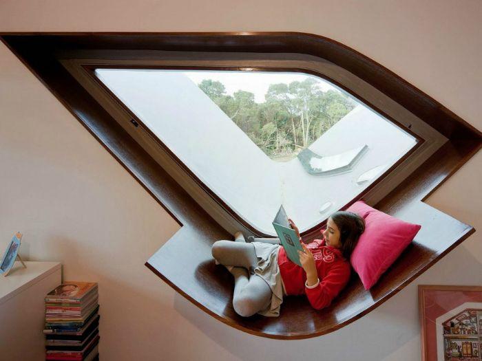 Egy eredeti formájú ablak és egy ablakpárkány, amely fel van szerelve olvasásra és pihenésre.