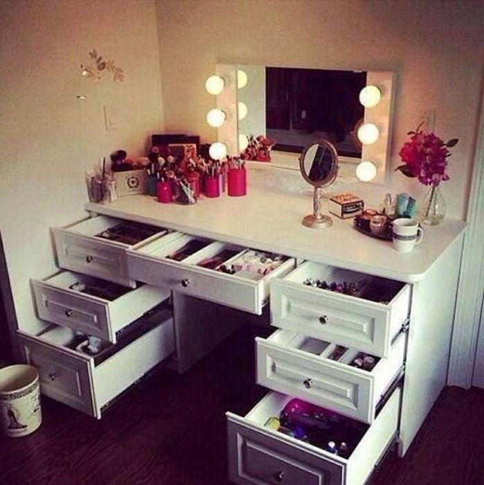 Шикарный столик с встроенным в зеркало освещением и множеством выдвижных ящиков.