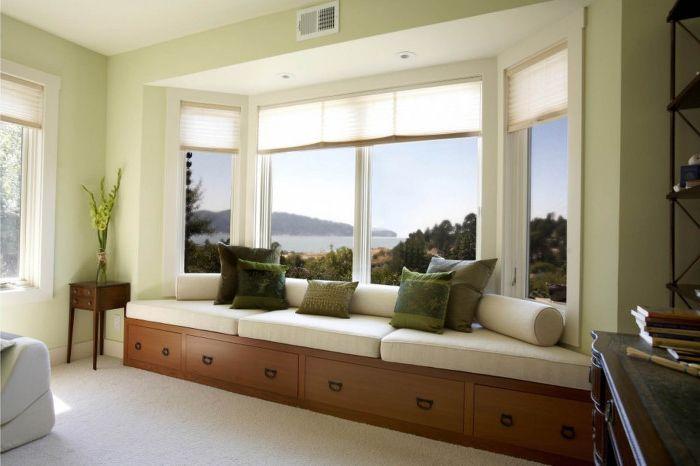 Елегантен бял диван на перваза на прозореца с наситени зелени възглавнички.