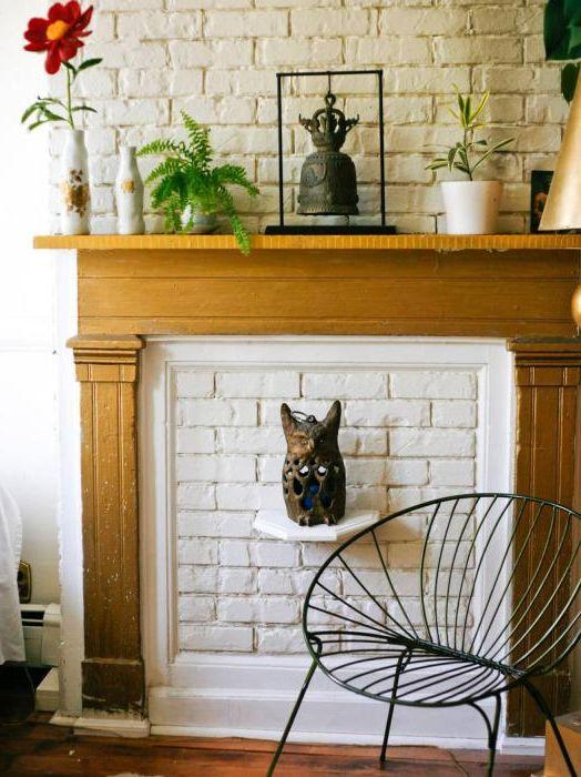 Śliczny sztuczny kominek w białej ścianie z cegły.