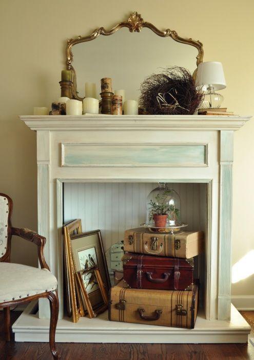 Elegancki ozdobny kominek z zabytkowymi walizkami i obrazami w środku.