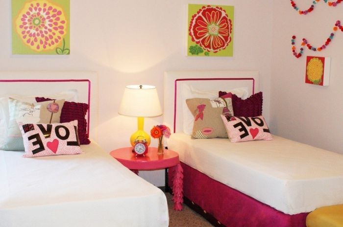Современная спальня для двух девочек с похожими декорациями возле каждой кровати.