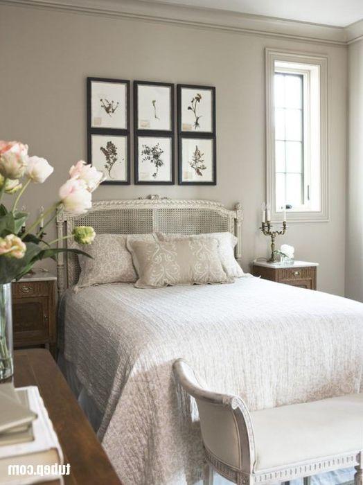 Стена над изголовьем кровати в традиционной спальне, украшенная шестью идентичными картинами.