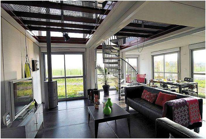 Къщата е много светла благодарение на огромните стъклени прозорци, които при необходимост могат да се затварят с врати за контейнери, които функционират като сигурни капаци.
