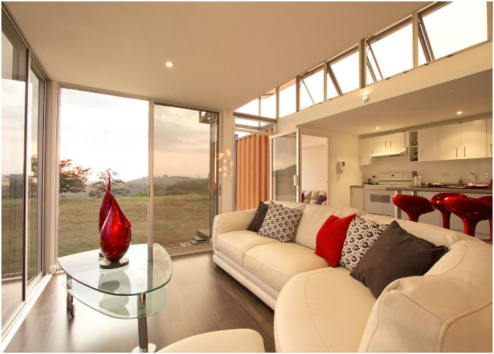 Большие окна и светлая внутренняя отделка дома без излишеств делают его просторным и уютным для проживания или отдыха.