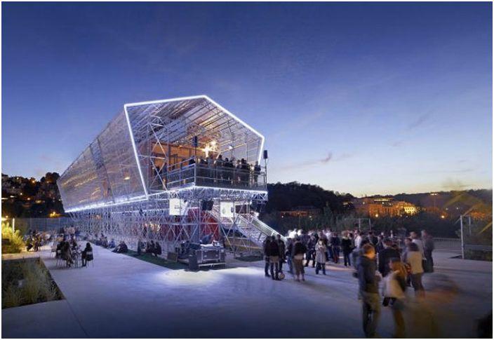 Удивителен архитектурен шедьовър, изграден от преобразувани контейнери за превоз, заобиколен от остъклен дървен скелет.
