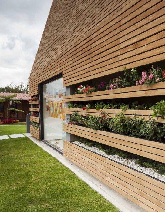 Wspaniały dom z ukwieconym ogrodem wbudowanym w ściany.