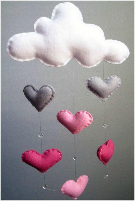 Обемен дъждов облак, изработен от плат, конци и мъниста, който може да се използва за украса на стените на детска стая.