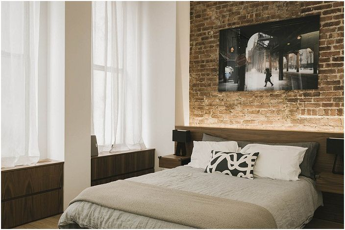 Тухлената стена в спалнята е плодороден фон за необичайни картини и плакати.