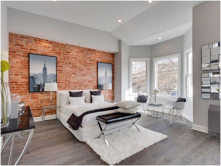 Ciepły naturalny kolor cegły w połączeniu z czarno-białymi tkaninami harmonizuje wystrój sypialni.