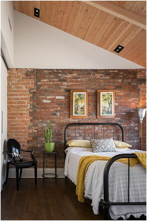 Dekoracja ceglanej ściany korzystnie podkreśla wysokie sufity sypialni.