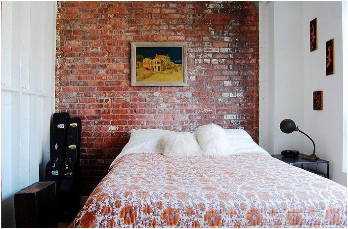 Красивата спалня е украсена с картини и каменни стени на стената, всички които перфектно подчертават домашната атмосфера.