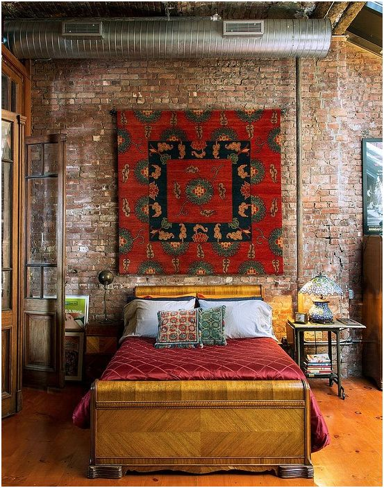 Тухлените стени се съчетават красиво с дървената и дъска настилка в спалнята.