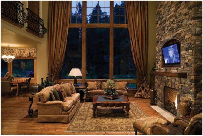 Високият таван в хола добавя пространство и красота към помещението, в което камината хармонично се отписва.