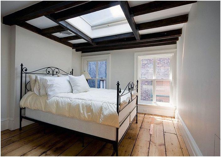 Przytulna sypialnia z piękną lukarną i szykownym sufitem dopełnia wnętrze pokoju.