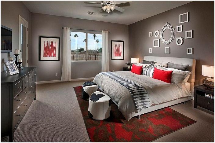 Спалнята в сиви тонове е инкрустирана с червени елементи в интериора и бели рамки на стената, които идеално се вписват в интериора.