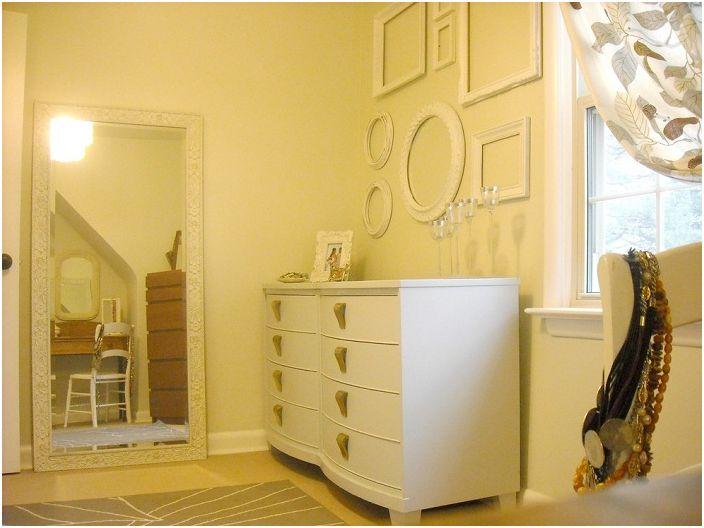 Pomieszczenie utrzymane jest w kremowej kolorystyce, ozdobione ramami, które dodatkowo rozjaśniają wnętrze.