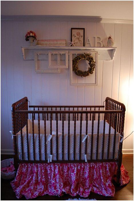 Pokój dziecinny ozdobiony jest ładnymi ramkami i półką w jasnych kolorach, praktycznym i jednocześnie ładnym.