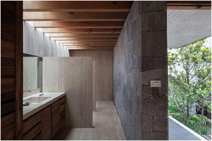 Niezwykła łazienka z ciekawym wnętrzem, które podkreśla ukryte oświetlenie i kamienna ściana.