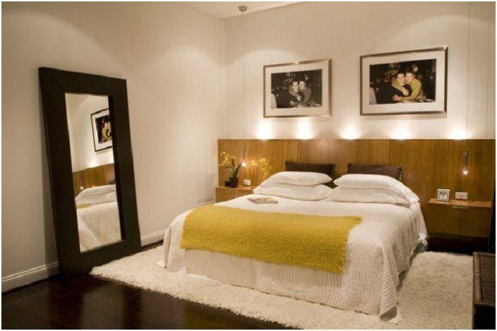 Wnętrze sypialni podkreśla oświetlenie wezgłowia łóżka.