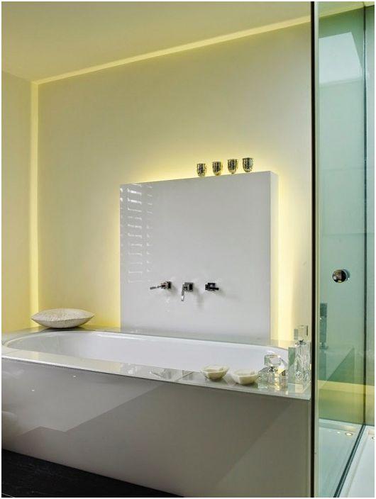 Niezwykłe wnętrze łazienki utrzymane w jasnych kolorach dopełnia ukryte oświetlenie.