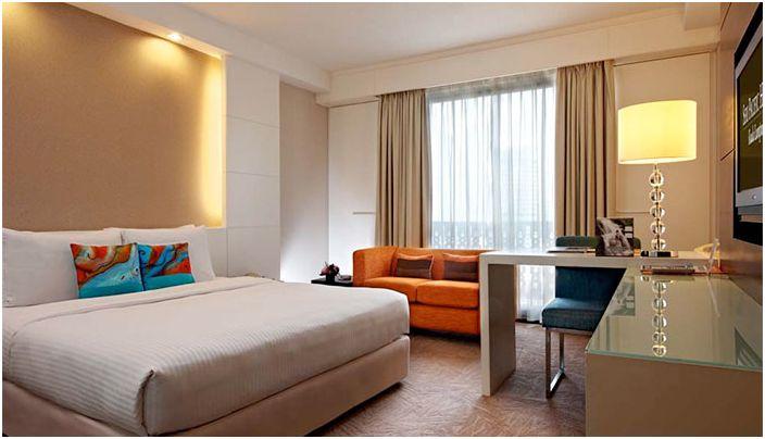 Ciepłe wnętrze sypialni tworzy oświetlenie pośrednie.