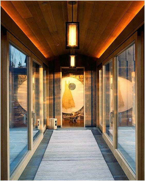 Zamknięty chodnik z drewnianym stropem i ciekawym oświetleniem łączy dwie strony domu.