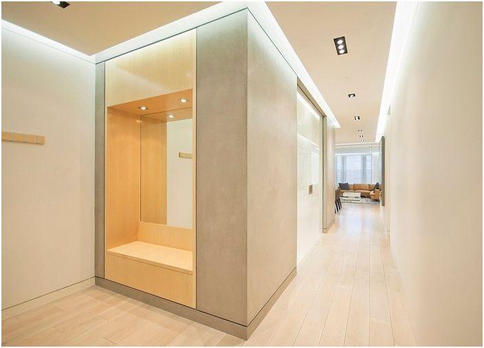 Kremowy hol wejściowy ozdobiony jest serią lamp, które tworzą w nim lekką atmosferę.
