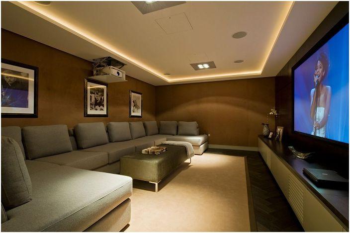 Pomieszczenie ze wspaniałym kinem domowym, uzupełnione ukrytym oświetleniem, które dodaje otoczeniu wyjątkowego uroku.