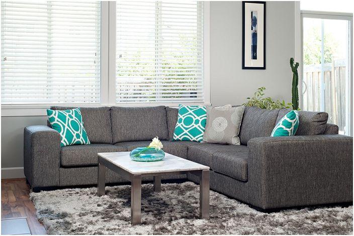 Urocza szara sofa z ciekawymi turkusowymi poduszkami, które zdobią wnętrze.