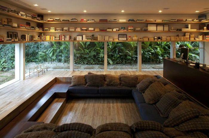Üvegfalakkal és egy nagy sziget-kanapéval könyvtár.