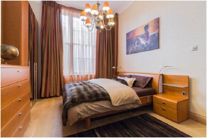 Спальня выполнена в персиковом цвете с нежной кремовой мебелью.