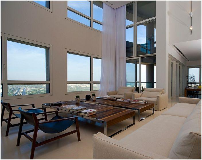 Аккуратная и утонченная комната гостиной с большим окнами и светлой мебелью, дополнена деревянными столиками.