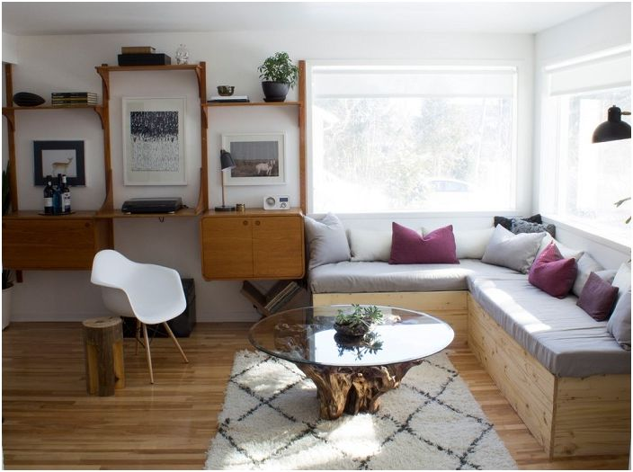 Гостиная оформлена в серо-лиловых тонах, а стеклянный столик стал просто находкой в таком интерьере.