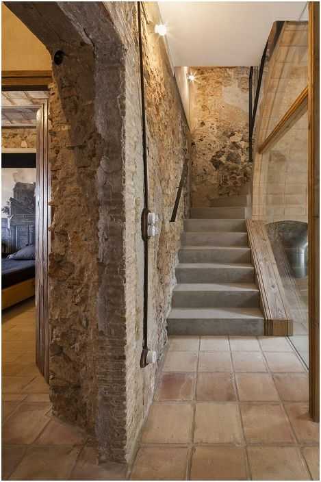 Интересният дизайн на стаята с необичайни каменни стени се допълва от стълбище в средиземноморски стил.