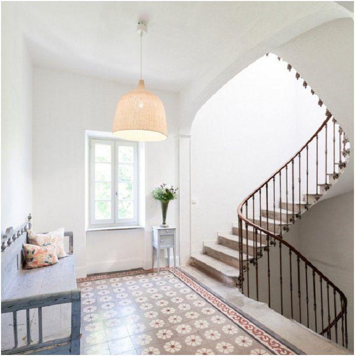 Den lyse atmosfæren i rommet er supplert med en lys grå trapp som harmonisk blandet inn i interiøret.