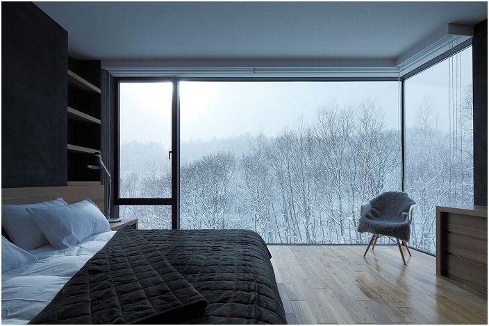 Спалня в черно и бяло с отлична гледка към заснежените дървета ще ви накара да се потопите в свят на фантазия и релакс.