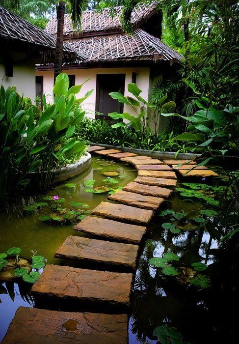 Красивая каменная дорожка посреди огромного пруда в саду.