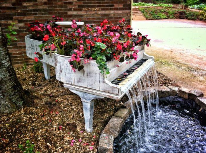 Малка цветна леха и водопад вътре стар музикален инструмент.