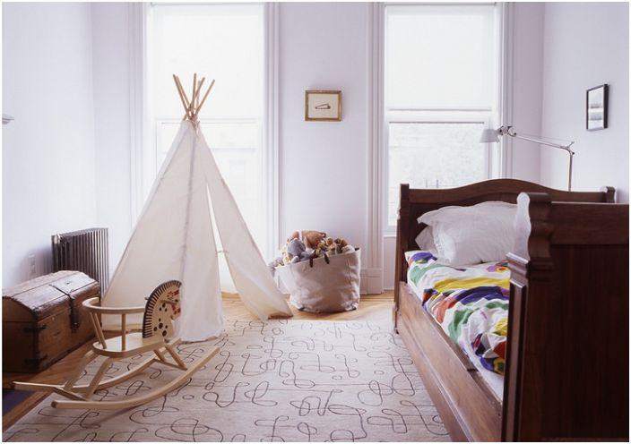 Стаята е в бели тонове, допълнена от дървени елементи и вигвам.