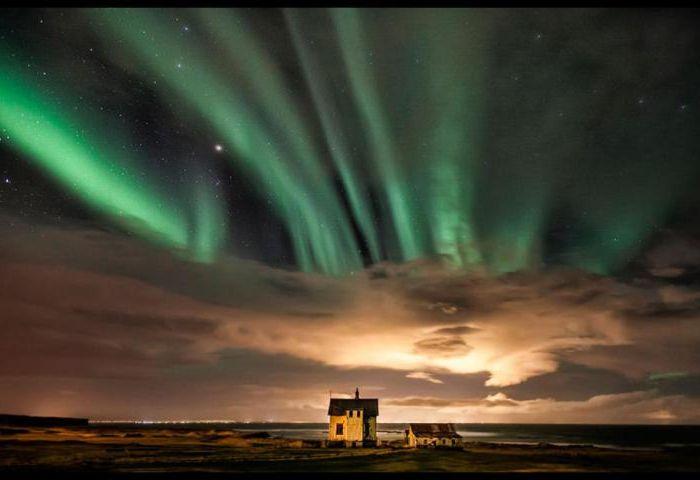 Samotna chata pod pięknymi zorzami polarnymi na nocnym niebie.