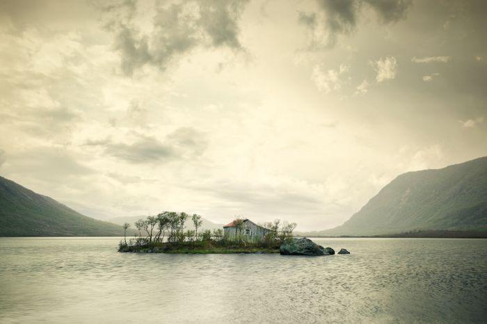 Samotny dom na maleńkiej wysepce na środku jeziora.