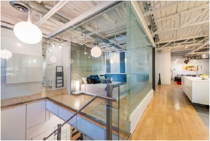 Пространството на спалнята се увеличава от стъклени стени, които разширяват концепцията за индустриален дизайн.