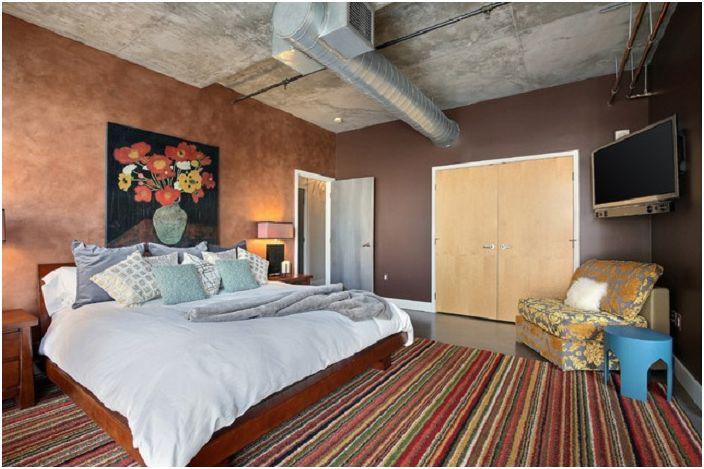 Спалня с нестандартен таван, което от своя страна ясно показва характеристиките на индустриалния стил в интериора.