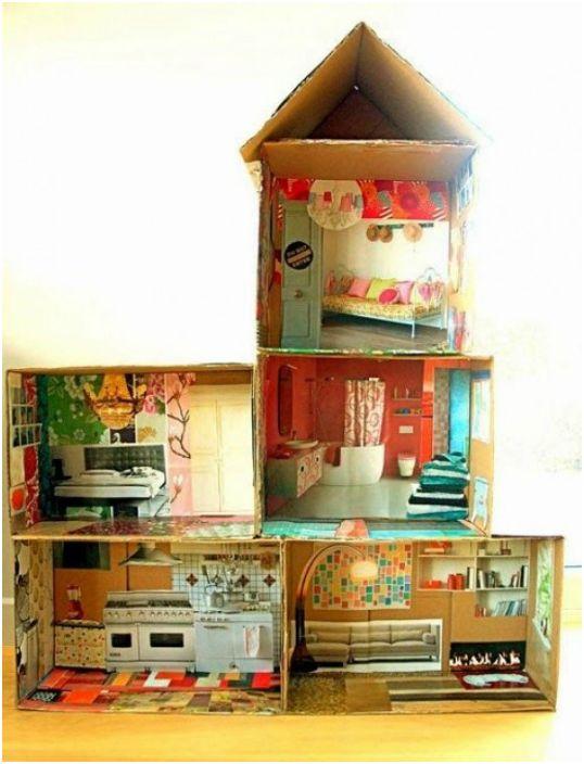 Трехэтажный домик из картонных коробок, украшенный вырезками из журналов.