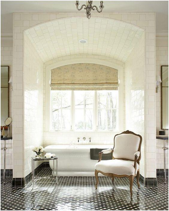 Прекрасна светла баня с бели плочки и огромен прозорец.