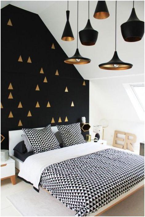 Czarna ściana ze złotym dekorem przypomina modne lampy