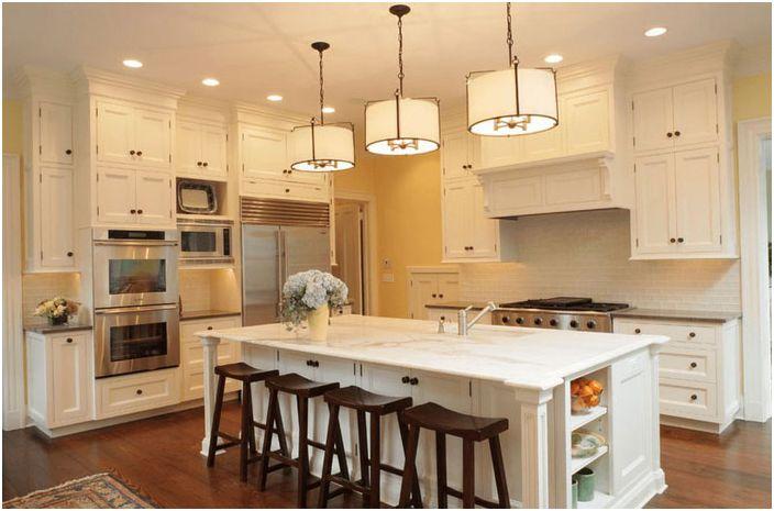 Hvit kjøkkenøy med mørke stoler